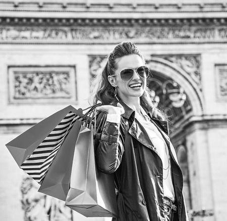 Stylish autumn in Paris. smiling elegant woman with shopping bags near Arc de Triomphe in Paris, France looking into the distance Stock Photo