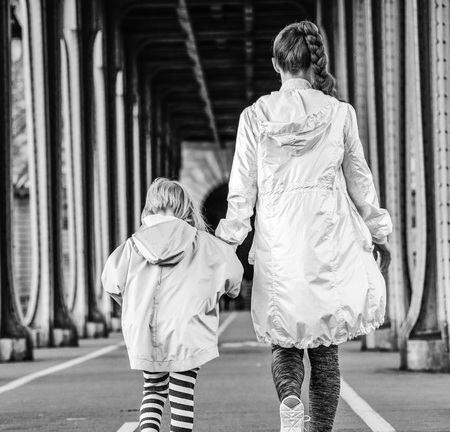 Year round fit & hip in Paris. Seen from behind healthy mother and child in sport style clothes on Pont de Bir-Hakeim bridge in Paris walking Stock Photo