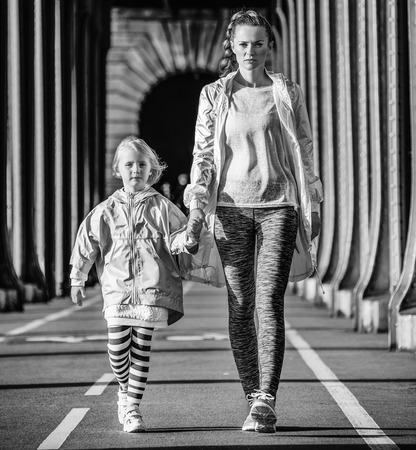 Year round fit & hip in Paris. Full length portrait of healthy mother and child in sport style clothes on Pont de Bir-Hakeim bridge in Paris going forward