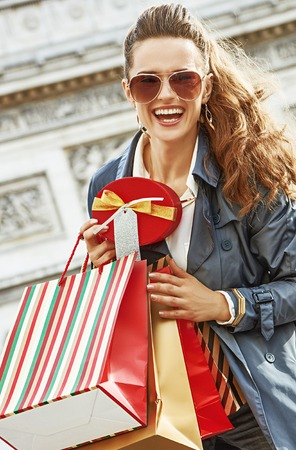 Stylish Christmas in Paris. smiling trendy woman with shopping bags and Christmas present box in Paris, France Stock Photo