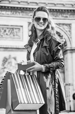 Stylish Christmas in Paris. smiling young woman in trench coat with shopping bags and Christmas present in Paris, France looking into the distance