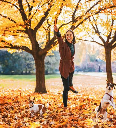 행복한 젊은 여자가 가을에 야외에서 노는 여자