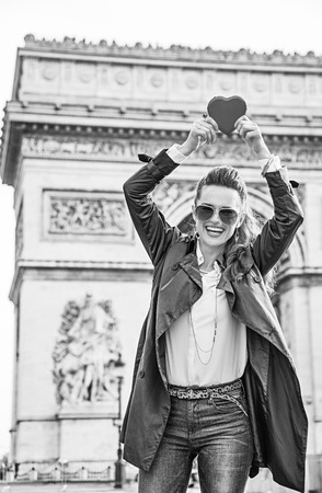 champs elysees: Stylish Valentines Day in Paris. Portrait of smiling young trendy woman in trench coat near Arc de Triomphe in Paris, France showing red heart shaped box of chocolates Stock Photo