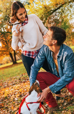 Happy young couple with dogs playing outdoors in autumn park Stock Photo