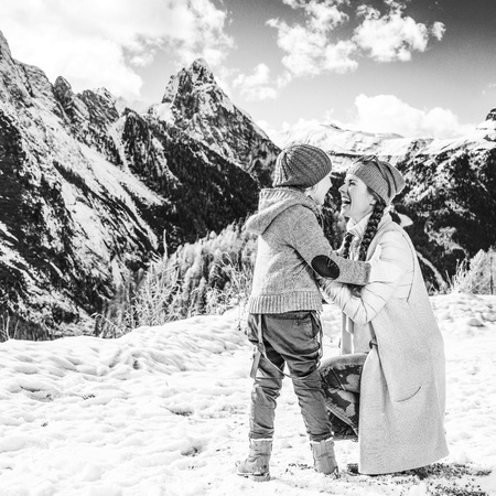 Winter on higher level of fun. Full length portrait of modern mother and daughter travellers against mountain landscape in Alto Adige, Italy playing