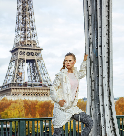 Year round fit & hip in Paris. young fit woman against Eiffel tower in Paris looking into the distance