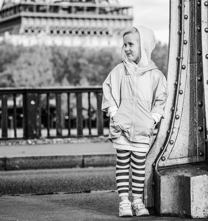 Year round fit & hip in Paris. Full length portrait of smiling active child in sport style clothes on Pont de Bir-Hakeim bridge in Paris looking aside
