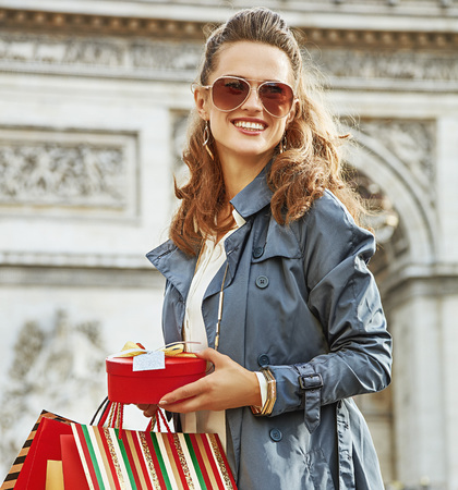champs elysees: Stylish Christmas in Paris. smiling young woman in trench coat with shopping bags and Christmas present in Paris, France looking into the distance