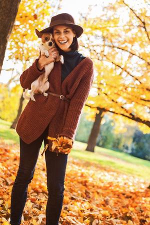 야외에서 개가 웃는 젊은 여자의 초상화 스톡 콘텐츠