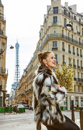 Boiling hot trendy winter in Paris. happy trendy fashion-monger with Christmas tree in Paris, France