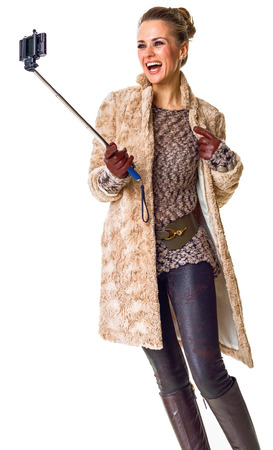 Winter things. smiling young woman in winter coat isolated on white taking selfie using selfie stick
