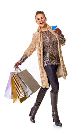 Winter things. Full length portrait of happy modern fashion-monger in winter coat isolated on white background with shopping bags showing credit card