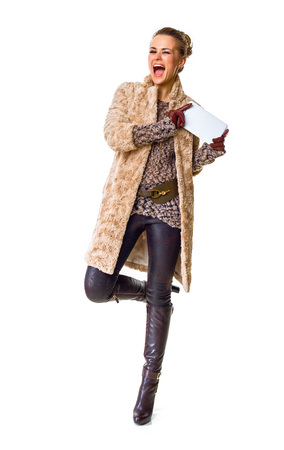 Winter things. Full length portrait of happy stylish fashion-monger in winter coat isolated on white with tablet PC