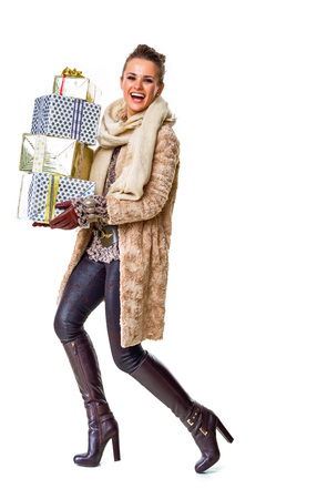 Winter things. Full length portrait of smiling modern fashion-monger in winter coat isolated on white with pile of Christmas present boxes walking