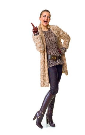 Winter things. Full length portrait of smiling young woman in winter coat isolated on white pointing at something