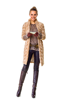 Winter things. Full length portrait of smiling modern fashion-monger in winter coat isolated on white writing sms