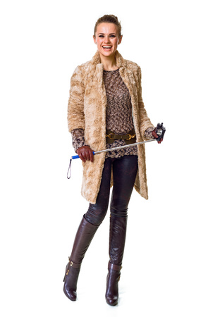 Winter things. Full length portrait of smiling trendy fashion-monger in winter coat isolated on white with selfie stick