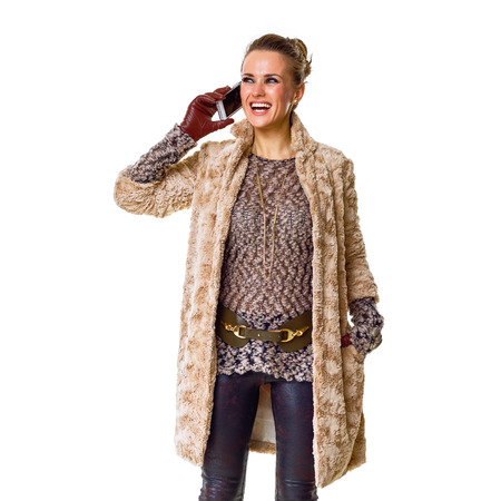 Winter things. Full length portrait of happy trendy fashion-monger in winter coat isolated on white talking on a smartphone