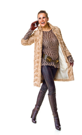 Winter things. Full length portrait of smiling trendy woman in winter coat isolated on white using a smartphone and walking