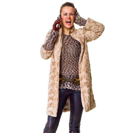 Winter things. Full length portrait of stressed young fashion-monger in winter coat isolated on white speaking on a mobile phone