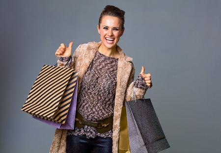 겨울 일들. 엄지 손가락을 보여주는 회색 배경에 고립 된 쇼핑 가방 겨울 코트에서 웃는 현대 여자의 초상화