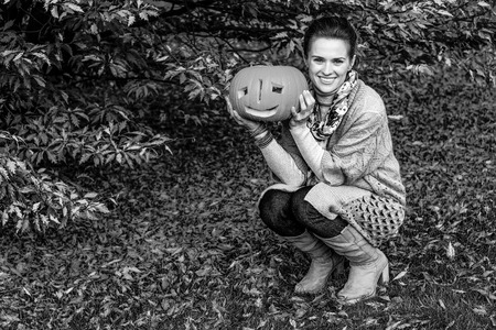 Trick or Treat. Portrait of happy young woman on Halloween at the park with pumpkin Jack O'Lantern
