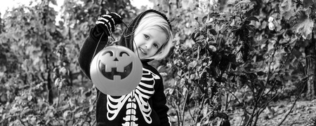 Trick or Treat. child wearing skeleton costume on Halloween outdoors showing pumpkin Jack O'Lantern basket