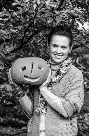 Trick or Treat. smiling modern woman on Halloween at the park showing pumpkin Jack OLantern