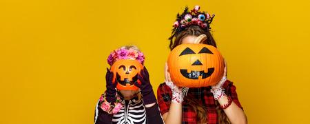 Colorido halloween. madre moderna y niño en traje de halloween de estilo mexicano aislado sobre fondo amarillo con calabazas jack-o-lantern delante de caras Foto de archivo - 88502637