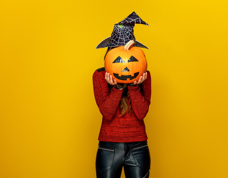 Colorful halloween. young woman in halloween witch costume isolated on yellow background holding sad jack-o-lantern pumpkin in the front of face