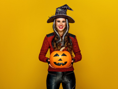 Colorful halloween. smiling young woman in halloween witch costume isolated on yellow background showing jack-o-lantern pumpkin