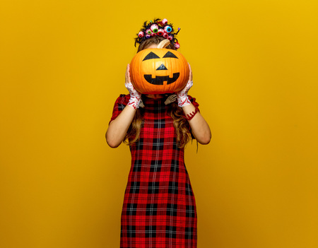 Colorful halloween. young woman in Mexican style halloween costume isolated on yellow holding jack-o-lantern pumpkin in the front of face Foto de archivo