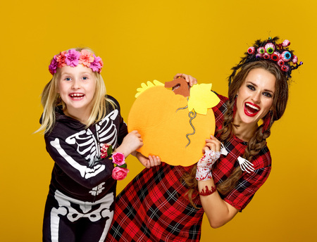 Colorful halloween. happy modern mother and child in Mexican style halloween costume on yellow background showing pumpkin Foto de archivo
