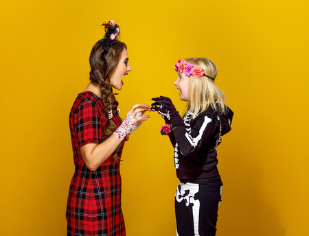 Colorful halloween. modern mother and daughter in Mexican style halloween costume isolated on yellow background frightening each other