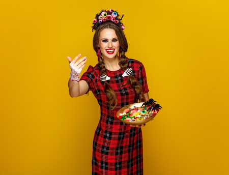 Colorful halloween. smiling modern woman in Mexican style halloween costume on yellow background with plate of Halloween candies calling to come closer