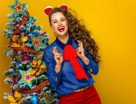 Festive season. happy trendy woman near Christmas tree isolated on yellow background with crossed fingers