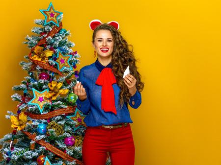 Festive season. smiling modern woman near Christmas tree isolated on yellow background holding nasal spray