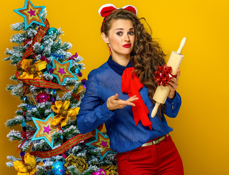 Festive season. young woman near Christmas tree isolated on yellow background unhappy with present Stock Photo