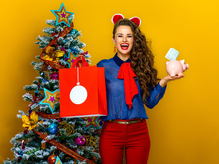 Festive season. smiling trendy woman near Christmas tree isolated on yellow background showing shopping bag and piggy bank with an euro bill Stock Photo