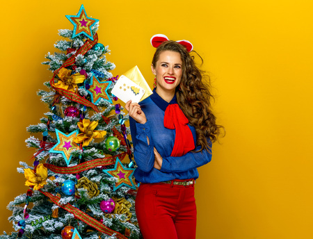 Festive season. smiling elegant woman near Christmas tree on yellow background with envelope and postcard