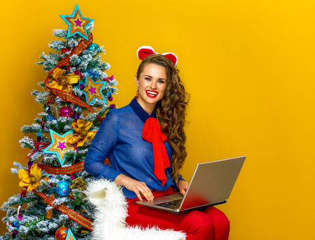 Festive season. happy young woman near Christmas tree isolated on yellow background sitting with laptop