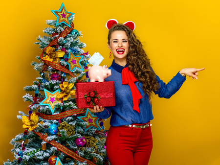 Festive season. happy young woman near Christmas tree isolated on yellow background pointing at something showing present box and piggy bank with an euro bill