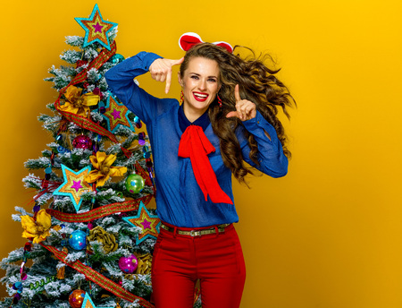 Festive season. happy modern woman near Christmas tree isolated on yellow background with hands framing
