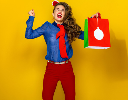 Festive season. smiling modern woman  isolated on yellow background with Christmas shopping bag rejoicing and jumping