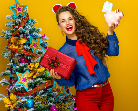 Festive season. happy young woman near Christmas tree on yellow background showing present box and piggy bank with an euro bill
