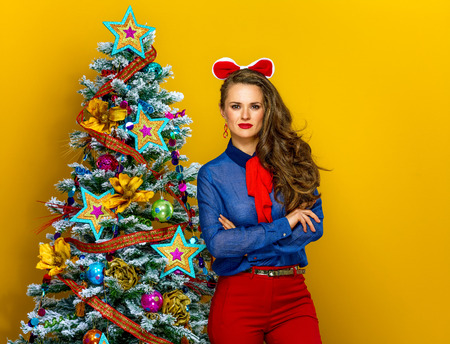 Festive season. Portrait of modern woman standing near Christmas tree on yellow background Stok Fotoğraf