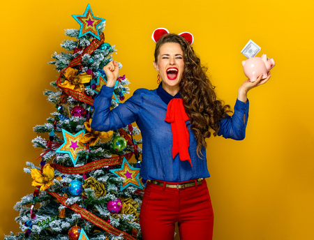 Festive season. happy stylish woman near Christmas tree isolated on yellow background with a piggy bank with a dollar bill rejoicing