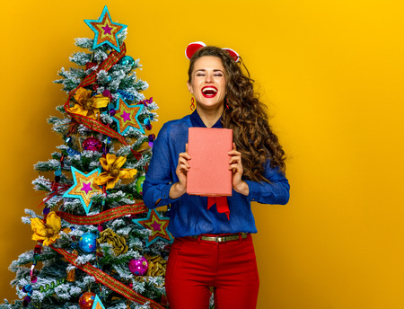 Festive season. smiling trendy woman near Christmas tree isolated on yellow background holding a book Stock Photo