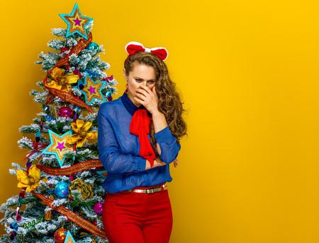Festive season. Portrait of stressed stylish woman standing near Christmas tree isolated on yellow background Stock Photo