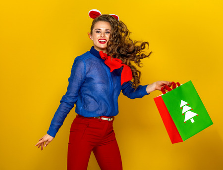 Festive season. happy modern woman on yellow background with Christmas shopping bag jumping Фото со стока